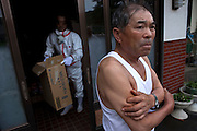 Mr Miura (52) from the NGO Heart Care Rescue, offering necessary supplies to Mr Shinichi Sano (75) who often spends time in his house which he had to evacuate as Iitate village has high levels of radiation.