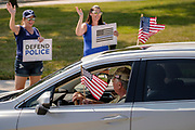 "08 AUGUST 2020 - WEST DES MOINES, IOWA: People line Mills Civic Parkway in front of the West Des Moines police station and cheer as a motorist flying American flags honks in support of them during a rally in support of police and law enforcement. About 100 people gathered at the West Des Moines Law Enforcement Center to rally in support of law enforcement. The rally was organized by ""Uplifting Our Police,"" a local organization that supports law enforcement. They rallied at Des Moines Police headquarters in July. They are planning similar rallies at police stations in the Des Moines metropolitan area.      PHOTO BY JACK KURTZ"