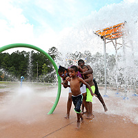 Ethan Clay, 6, of Tupelo, runs away from his sister Z'mya, 10, brothers Z'mon, 11, and Kameron, 8, as the large water bucket dumps water on them as they play at the splash pad at Theron Nichols Park in Tupelo on Wednesday afternoon. The clay siblings came out to enjoy a day in the water after eating lunch together as their days out of school for the summer come to a close.