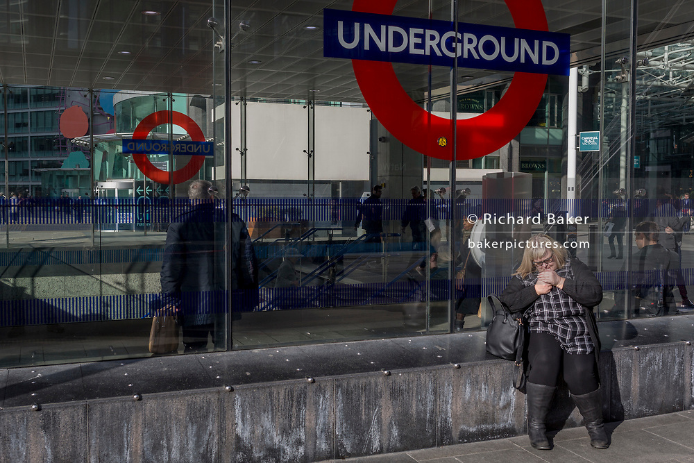 A woman lights a cigarette outside the newest entrance to Victoria underground station, on 11th March 2019, in London, England.