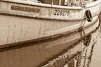 A  black-and-white photo of a boat and reflection in the fishing village of Wanchese NC.