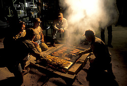 Stock photo of a group of men cooking big steaks on their outdoor grill at night