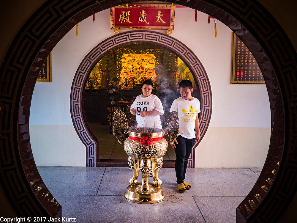 28 JANUARY 2017 - SAMUT PRAKAN, SAMUT PRAKAN, THAILAND: Boys light incense before the Chinese New Year Lantern Festival at the Tham Katanyu Foundation shrine in Samut Prakan, a suburb about 15 miles from Bangkok. More than 5,000 handmade lanterns imported from Taiwan are hung on the grounds of the shrine. Some of the lanterns are traditional Chinese lanterns, others are in the shapes of people or deities. There is also traditional Chinese entertainment, likes lion dances, at the festival.     PHOTO BY JACK KURTZ