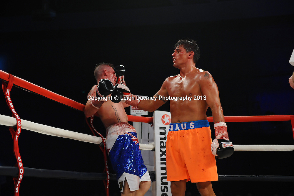 Albert Kraus (orange shorts) defeats Nicky Jenman in a boxing contest at Glow, Bluewater, Kent, UK. Hennessy Sports. 16.11.13. © Leigh Dawney Photography 2013.