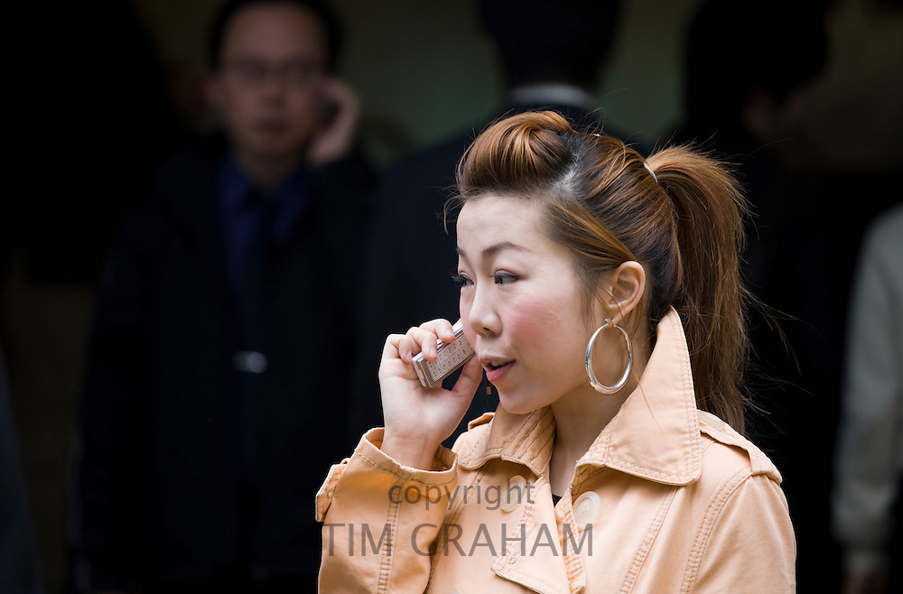 Young woman using cellphone in old Chinese district, Sheung Wan, Hong Kong, China