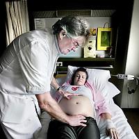 Nederland,Tilburg ,30 mei 2008.Verloskundige Paul Reuver bekijkt en voelt de buik van een zwangere vrouw in het Elisabethziekenhuis..Obstetrist Paul Reuver looks at and feels the abdomen of a pregnant woman.