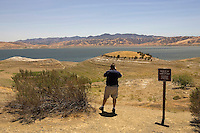 GUSTINE, CA - JULY 16:  A man stops to take a photo of the San Luis Reservoir on July 16, 2007 in Gustine California. The governor stressed the importance of a comprehensive water plan as the current system is not prepared to handle the population growth projected for the next 50 years. The reservoir which is filled to just 20.797 percent of capacity and is down 186 feet from normal levels supplies water for the Silicon Valley, Central Valley farms and Southern California homes and businesses.  (Photograph by David Paul Morris)