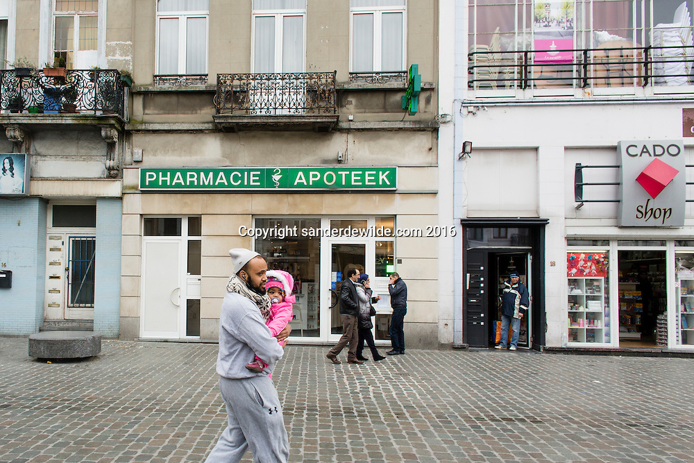 20160319 story on the streets and people of Molenbeek, after Salam Abdeslam was arrested a day before. A man holding his child passes by