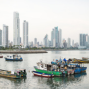 Old wooden fishing boats anchored in a protected harbor, with the modern skyscrapers of Punta Paitilla in the background on the waterfront of Panama City, Panama, on Panama Bay.