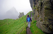 Young woman hiking in Mykines island, Faroe Islands