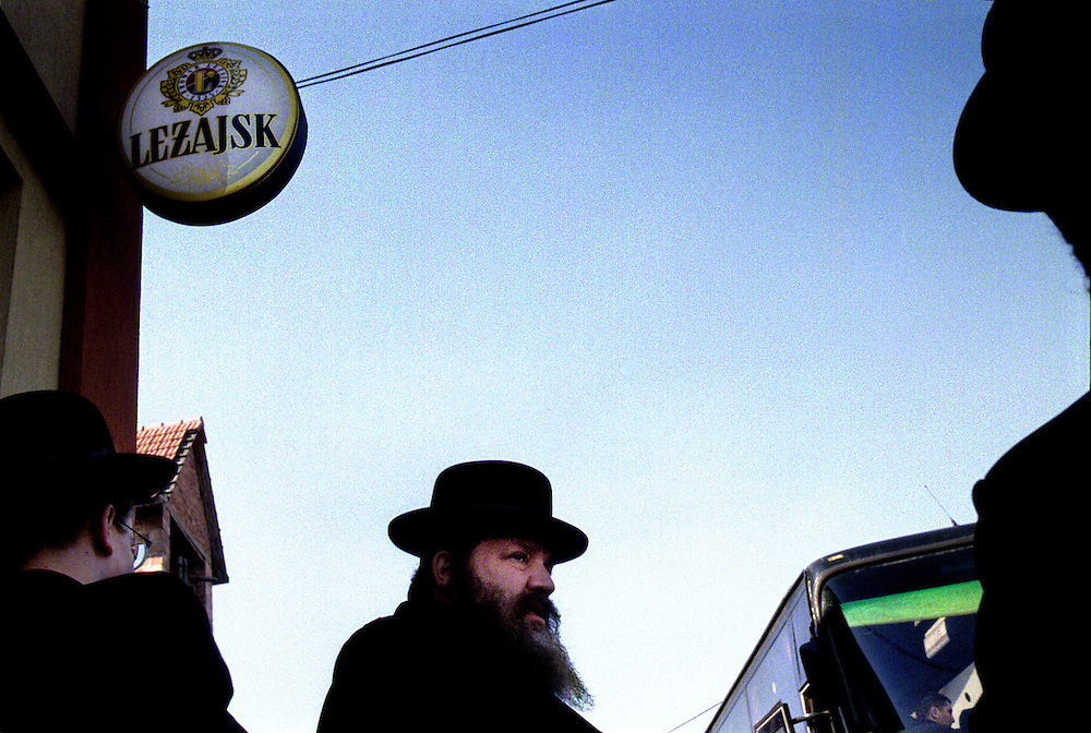 .030324-25 The 21 of Adar (usually in March) each year, tens of thousands hassidic jews from all over the world travel to the small town of Lezajsk in Poland. Most of them come in chartered airplanes from New York and Israel. They come to pray to the soul of Rabbi Elimelech, a holy man who died in Lezajsk 1787. In the 18th century Lezajsk was the center of hassidism in Poland. Today there are no hassidic jews left living here. The obejctive of the yearly pilgrimage is to pray to to the soul of Rabbi Elimelech which is believed to descend to Earth on the day of his death.  For those who are not allowed to enter burial grounds, tents for prayer are raised nearby. Women are not allowed in the central space of the tomb. Some of them pray by the outside walls, some pray in a designated room inside. The pilgrims gather by thousands in the small and incredibly crowded and overheated tomb and spend the entire night in fervent prayer, before they eat and quickly depart for the nearby airports in chartered buses ....030324-030325 Bussar går i skytteltrafik till och från flygplatserna i regionen. De flesta chassiderna kommer till Lezajsk med chartrade flygplan från New York och Israel. Så fort de anlänt börjar de bönen och slutar inte förrän många timmar senare då de äter i den stora matsalen och genast flyger hem.  Ofta tar hela resan inte mer än 24 timmar. De som inte själva har råd att betala resan får den ofta finansierad via gåvor och insamlingar.The 21 of Adar (usually in March) each year, tens of thousands hassidic jews from all over the world travel to the small town of Lezajsk in Poland. Most of them come in chartered airplanes from New York and Israel. They come to pray to the soul of Rabbi Elimelech, a holy man who died in Lezajsk 1787. In the 18th century Lezajsk was the center of hassidism in Poland. Today there are no hassidic jews left living here. The obejctive of the yearly pilgrimage is to pray to to the soul of Rabbi Elimelech which is belie