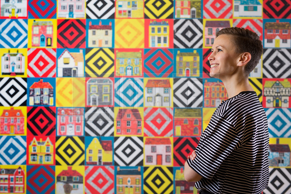 "© Licensed to London News Pictures. 15/06/2017. Wakefield UK. Picture shows Kerry Chase from the Yorkshire Sculpture park looking over a wall hanging screen printed ""quilt"" by Illustrator Alice Pattullo. Alice Pattullo has a new exhibition at the Yorkshire Sculpture park called Of House & Home which is her most ambitious project to date & includes 60 new screen printed editions revealing Pattullo's fascination with traditions, superstitions & folklore. The exhibition takes visitors on a journey through a victorian household from garden to parlour culminating with the heart of the home a recreation of a traditional fireplace & mantlepiece. Photo credit: Andrew McCaren/LNP"