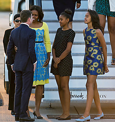© Licensed to London News Pictures. 15/06/2015. Stansted, UK. First Lady MICHELLE OBAMA with Daughters MALIA SASHA,  is greeted by U.S. Ambassador to th UK, Matthew W. Barzun (left), as she arrives in the UK at Stansted Airport  for the start of a three day visit to the UK. During the visit the First Lady and her family will meet with students at Mulberrry School for Girls and have Tea with Prime Minister David Cameron and Samantha Cameron. Photo credit: Ben Cawthra/LNP