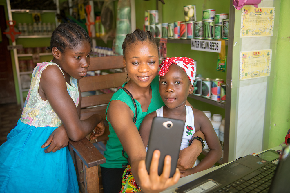 Young girls take a selfie in a store in Ganta, Liberia