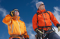 Two mountain climbers standing outdoors one using walkie-talkie