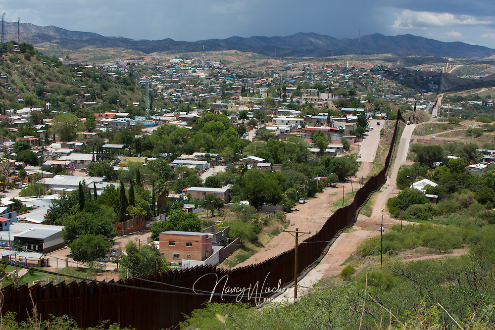 The international border fence snakes along hills in this view from east of Nogales, Ariz. Nogales in Sonora, Mexico, is more densely populated than that of its U.S. sister city. Photo taken July 16, 2014. NANCY WIECHEC
