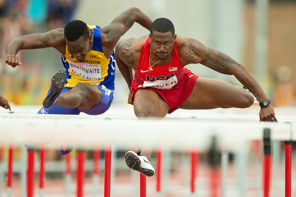 David Oliver of the United States leads the field during the final of the 110 metre hurdles at the 2015 Pan American Games at CIBC Athletics Stadium in Toronto, Canada, July 24,  2015. Oliver won the gold medal and set a new Pan American Games record of 13.07s.  AFP PHOTO/GEOFF ROBINS