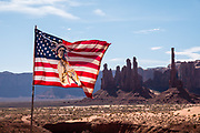 An American Flag, designed with a Native American Indian holding a peace pipe, waves in the breeze at Monument Valley Navajo Tribal Park, Arizona, USA.