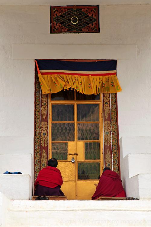 Asia, Bhutan, Thimpu. Buddhists at doorway of the Memorial Chorten in Thimpu.