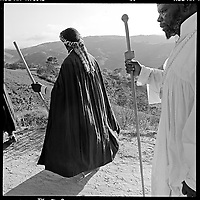 Church elders - Vangeli, or Evangelists - of the Nazareth Baptist Church carrying the Communion artifacts they refer to as the Ark, lead over 100,000 members along a sand road on the first day their annual three day bare-foot pilgrimage from the church headquarters near KwaMashu to the holy mountain of Nhlangakazi, KwaZulu natal, January 1998. The pigrimage traces th footsteps and pays homage at shrines of the founder Isaiah Shembe's 1913 journey of enlightenment. Photo Greg Marinovich