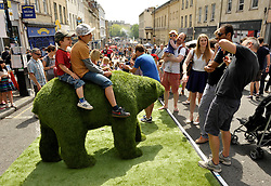 © Licensed to London News Pictures. 01/06/2014; Bristol, UK.  Children sit on a grass bear as Bristol's famous Park Street is turned into a pedestrianised park for the Make Sunday Special series of events by Bristol's elected Mayor George Ferguson, once a month in the summer.  Artificial grass was laid out and stalls and entertainment provided.<br /> Photo credit: Simon Chapman/LNP