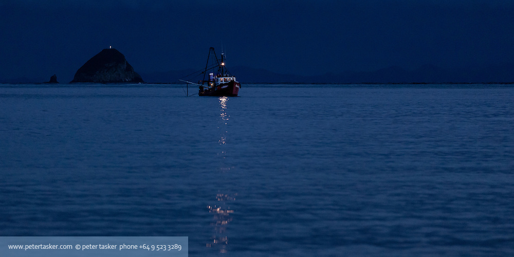 Night photograph of fishing trawler Corinthian preparing for an early morning departure from Port Jackson, Coromandel Peninsula, Hauraki Gulf, New Zealand. Channel Island in background and Great Barrier Island on the horizon.