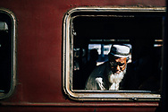 An older man peers out of a window at the train station of Kandy, Sri Lanka, Asia
