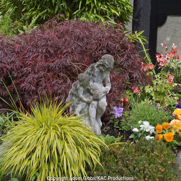 "A statue of ""The Reading Lesson"" sits amongst a Japanese maple, grasses and flowering plants"