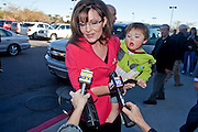"Dec. 1, 2009 -- TEMPE, AZ: SARAH PALIN and her son, TRIG, arrive at the Costco in Tempe, AZ, Tuesday, Dec. 1. Former Alaska Governor Sarah Palin signed copies of her book, ""Going Rogue"" at a Costco in Tempe, AZ, Tuesday. More than one thousand people showed up for the signing. About 150 of them spent the night at the store. Palin did not make any comments or speak to the address during her appearance in Tempe.  Photo by Jack Kurtz"