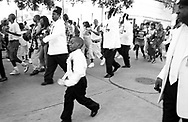 A young boy is walking and dancing along with a Second line. New Orleans, USA, 2004