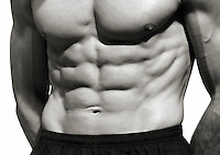 The torso and flexed abdominals of a muscular young man.
