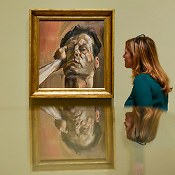 "© Licensed to London News Pictures. 23/10/2019. LONDON, UK. A staff member views ""Man's Head (Self-Portrait)"", 1963, by Lucien Freud. Preview of ""Lucian Freud: The Self-portraits"" at the Royal Academy of Arts in Piccadilly.  56 works on display chart Freud's artistic development over almost seven decades on canvas and paper in a show which runs 27 October to 26 January 2020.  Photo credit: Stephen Chung/LNP"