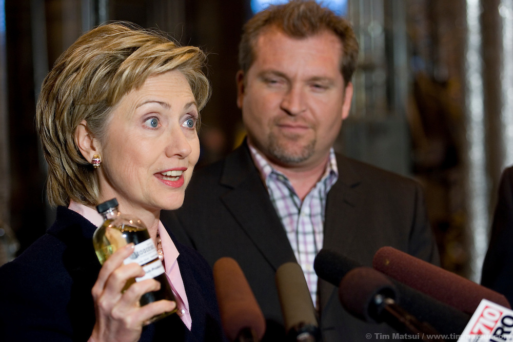 """SEATTLE, WA - Friday, January 27, 2006 U.S. Senator Hillary Clinton (D-NY) holds a bottle of pure B100 biodiesel while Seattle Biodiesel president and founder John Plaza looks on. Clinton joined U.S. Senator Maria Cantwell (D-WA) at Seattle Biodiesel to promote energy independence and call for a greater federal support for ground-brakening alternative energy initiatives already underway at the local level. Cantwell is signing on to Clinton's legislation to create a latter-day """"Manhattan Project"""" aimed at accelerating the development of advanced energy technologies.  The two senators, with democratic leader Harry Reid (D-NV) are sponsoring the Advanced Research Projects Energy (ARPA-E) Act to fund alternative energy research. Cantwell states that reliance on foreign oil is a threat to the U.S. economy, competitiveness, and national security and she supports development of non-petroleum based fuels and energy sources. Seattle Biodiesel is working with Cantwell and Washington Governor Gregoire to help develop a market for biodiesel and recently signed a fuel contract with the Port of Seattle. Negotiations are currently underway for Seattle Biodiesel to expand its operations to create the nation's largest biodiesel refinery and to do so on Port property. Clinton is also in the Pacific Northwest to support her fellow democrats at fundraisers and to solidify her support. (Photo by Tim Matsui/WpN)"""