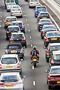 Motorcyclist slips through two lanes of traffic congestion on M25 motorway, London, United Kingdom