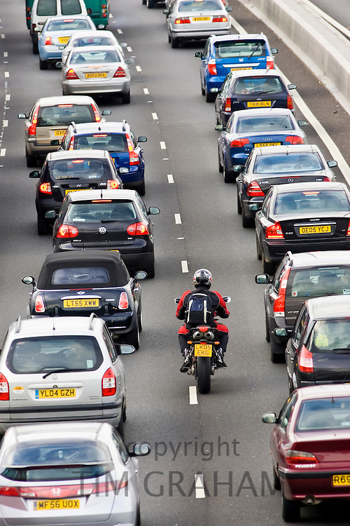 Motorcyclist slips through two lanes of traffic congestion on M25 motorway, London, United Kingdom