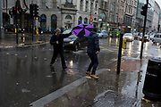 Storm Georgina swept across parts of Britain and in central London, lunchtime office workers were caught out by torrential rain and high winds, on 24th January 2018, in London, England. Pedestrians resorted to leaping across deep puddles at the junction of New Oxford Street and Kingsway at Holborn, the result of overflowing drains. Fourth in a sequence of seven photos.