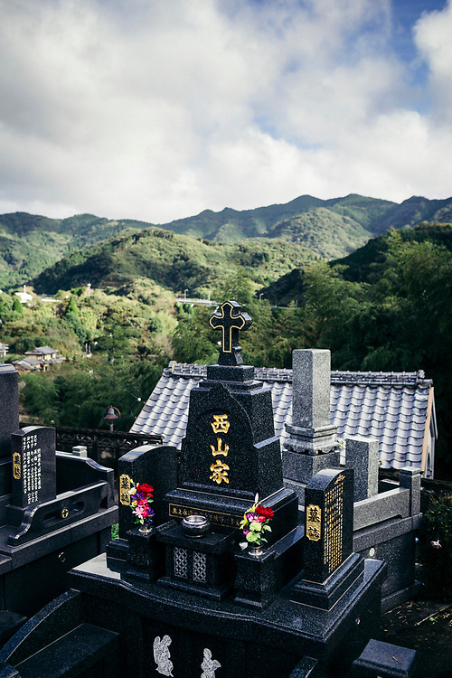 A Christian graveyard and distant mountains in Amakusa, Japan.