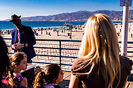 Entertainer on Santa Monica Pier waiting for audience reaction with replicas of crosses on graves in the background.