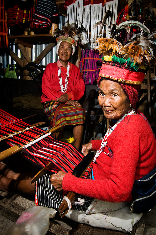 PHILIPPINES (Banaue, Province of Ifugao). 2009. Old Ifugao women weaving in a souvenir shop near Banaue.
