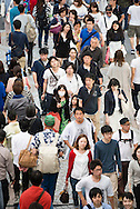 Elevated view of a crowd of people walking along pavement in Shinjuwu district of Tokyo, Japan. Large group of Japanese people.