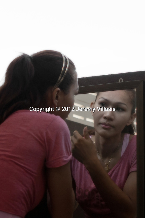 Nong Toom checks herself out on the mirror. With her mind and body in sync, Nong Toom has no regrets about her sex change.  Although she is happier now, she believes that part of feeling truly feminine depends on how much society is willing to accept her identity.