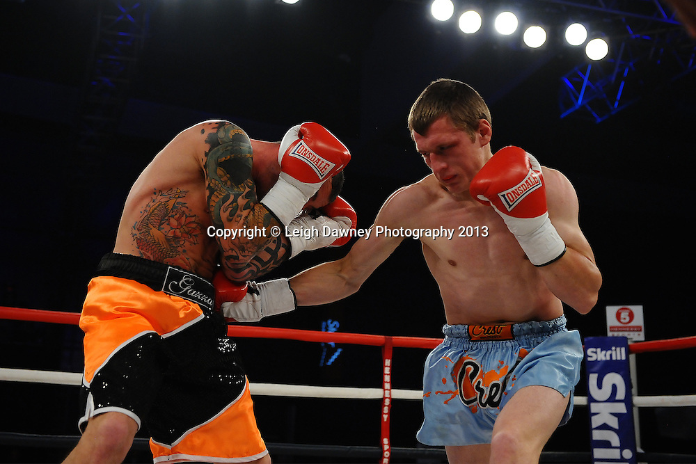 Garry Neale takes a shot by Simas Volosinas in a Light Welter weight contest. Glow, Bluewater, Kent, UK. Hennessy Sports © Leigh Dawney Photography 2013.