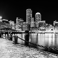 Boston cityscape at night black and white photo with the Boston Harborwalk waterfront, downtown Boston skyline and Northern Avenue Bridge. Boston Massachusetts is a major American city in the Eastern United States of America.