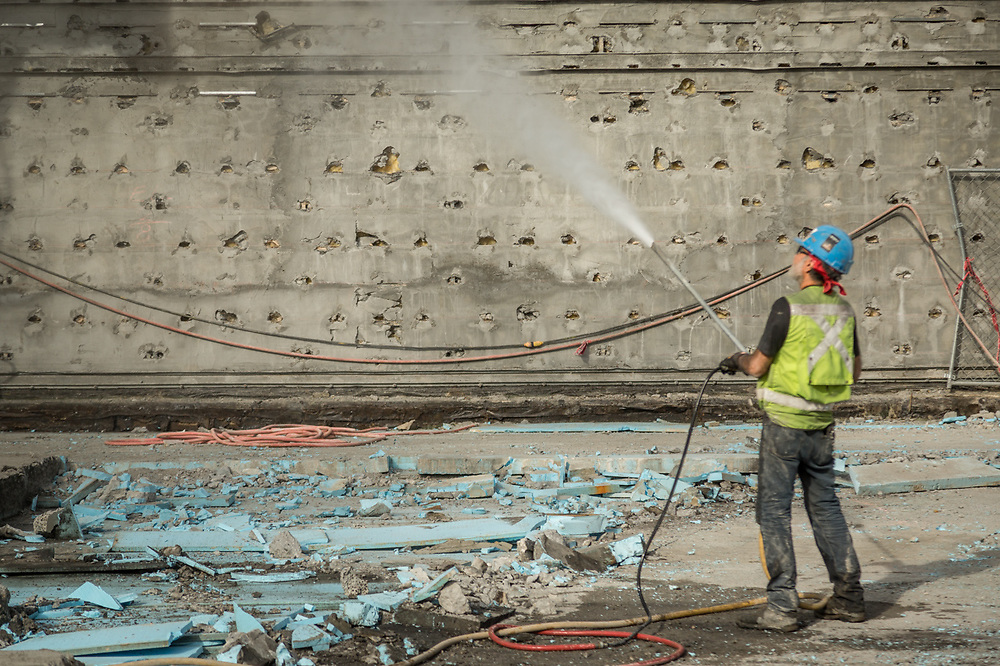 A construction worker waters down debris during a demolition project near the Moscone Center in San Francisco.