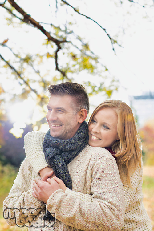 Portrait of beautiful woman hugging her husband from behind in park