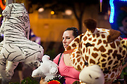 "01 SEPTEMBER 2011 - ST. PAUL, MN:  A woman with a stuffed animal on the midway at the Minnesota State Fair. The Minnesota State Fair is one of the largest state fairs in the United States. It's called ""the Great Minnesota Get Together"" and includes numerous agricultural exhibits, a vast midway with rides and games, horse shows and rodeos. Nearly two million people a year visit the fair, which is located in St. Paul.  PHOTO BY JACK KURTZ"