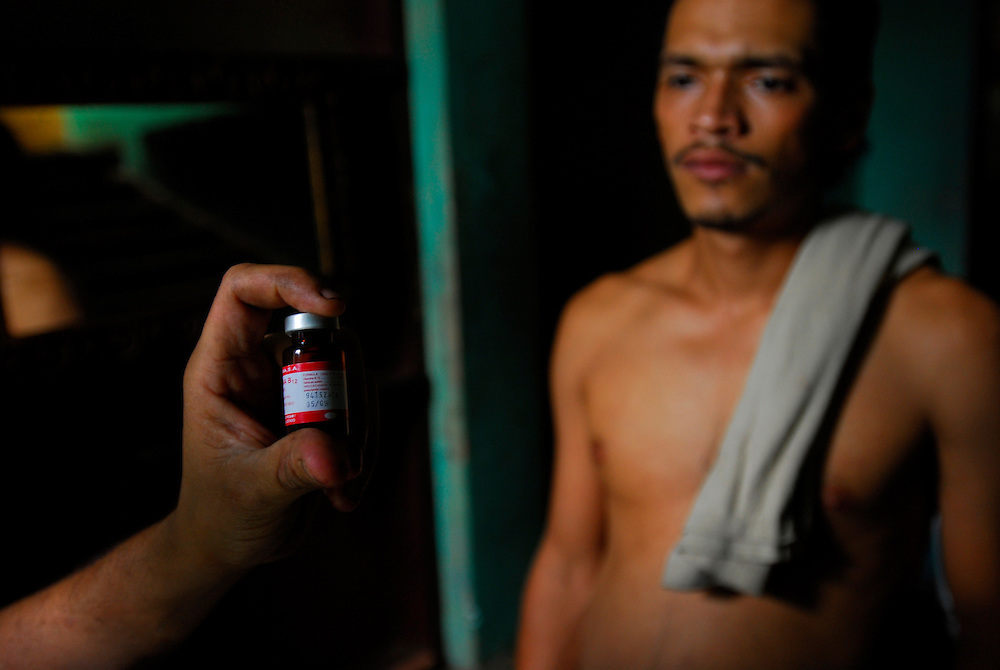 """Heber Bersario Acevedo, 25, looks at a vial of vitamin B complex at Casa Hogar, a rehabilitation home for alcohol and drug addicts, outside of Antigua, Guatemala. Acevedo has been living at Casa Hogar for one month and was heavily smoking crack and marijuana """"for years"""" when he decided to seek treatment for his addiction...Casa Hogar currently houses 44 men (with a maximum of 60.) Jorge Rosales, himself a former drug user, founded the home 2 years ago after he kicked his habit and left the garbage dump he had been living in for thirteen months...If accepted into Casa Hogar the voluntary residents must first spend 6 days in a first floor room of mattresses, are denied showers and must eat meals separately from other residents. Patients in the first floor zone suffer from convulsions, vomiting and other withdrawal symptoms and are monitored round the clock by a nurse. Most alcoholics who enter the program have been drinking rubbing alcohol, according to Rosales, because it is so inexpensive...""""If they make it"""" says resident Byron Rosales, """"they can join us up top."""" It is up to the individual when they feel they are ready to leave the home."""