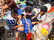 "30 AUGUST 2016 - BANGKOK, THAILAND: Children play a Thai version of the game ""jacks""  after a food and clothing distribution at the Poh Teck Tung shrine on the last day of Hungry Ghost Month in Bangkok. Chinese temples and shrines in the Thai capital host food distribution events during Hungry Ghost Month, during the 7th lunar month, which is usually August in the Gregorian calendar.         PHOTO BY JACK KURTZ"