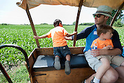 Brian Fuller sits with his son, Willem, 4, while also spotting a risky Holden Miller, 5, who is determined to see the horse-drawn wagon wheels roll during the fourth annual International Student Farm Outing at the Schultz Family Farm in Cottage Grove, Wis., on June 24, 2012. Co-sponsored by the Schultz family and the University of Wisconsin-Madison International Student Services (ISS), the event introduced more than 100 UW-Madison international students and their families, and friends of the Schultz family to agricultural life in rural Wisconsin.