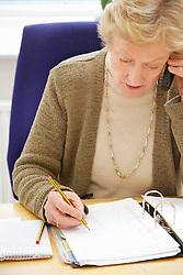 Senior Businesswoman Sitting at Desk Using Telephone
